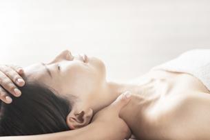 エステサロンで頭と首をマッサージされる若い女性の写真素材 [FYI04867827]