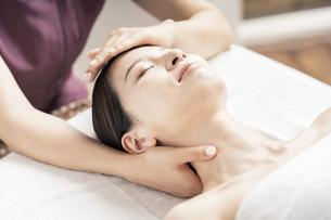 エステサロンで頭と首をマッサージされる若い女性の写真素材 [FYI04867828]