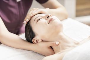 エステサロンで頭と首をマッサージされる若い女性の写真素材 [FYI04867829]