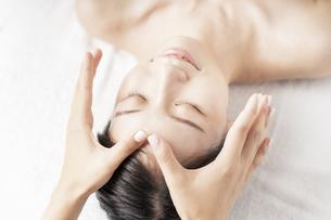 エステサロンで顔をマッサージされる若い女性の写真素材 [FYI04867832]