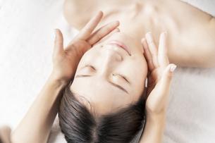 エステサロンで顔をマッサージされる若い女性の写真素材 [FYI04867833]