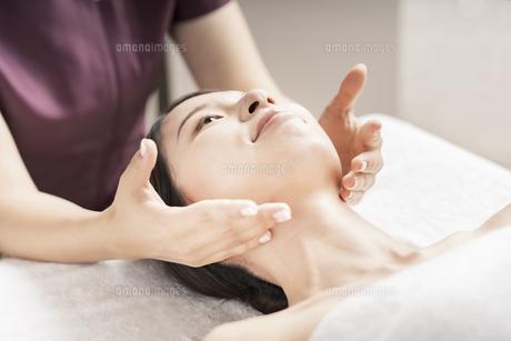 エステサロンで顔をマッサージされる若い女性の写真素材 [FYI04867834]