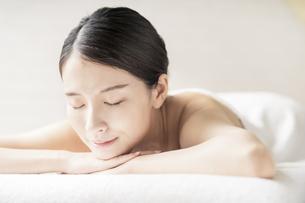 明るい雰囲気のエステサロンで横になる若い女性の写真素材 [FYI04867835]
