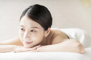 明るい雰囲気のエステサロンで横になる若い女性の写真素材 [FYI04867836]