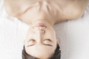 明るい雰囲気のエステサロンで横になる若い女性の写真素材 [FYI04867837]