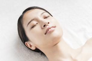 明るい雰囲気のエステサロンで横になる若い女性の写真素材 [FYI04867839]
