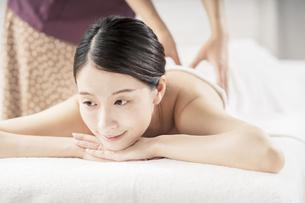 明るい雰囲気のエステサロンでマッサージを受ける若い女性の写真素材 [FYI04867842]