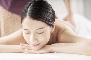 明るい雰囲気のエステサロンでマッサージを受ける若い女性の写真素材 [FYI04867844]