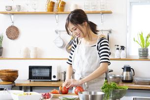 キッチンで料理を作る若い女性の写真素材 [FYI04867848]