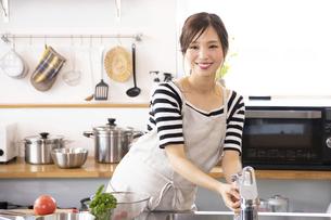 キッチンで料理を作る若い女性の写真素材 [FYI04867862]