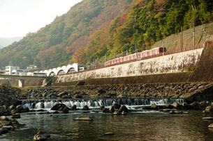 秋の箱根を走る車両と早川の写真素材 [FYI04868317]