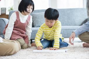 カーペットの上で絵を書く男の子の写真素材 [FYI04868351]