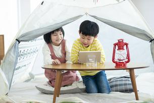 家の中のテントで遊ぶ姉弟の写真素材 [FYI04868358]