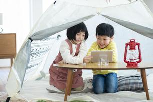 家の中のテントで遊ぶ姉弟の写真素材 [FYI04868359]