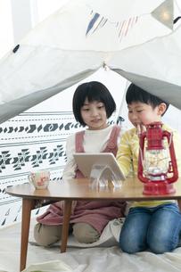 テントの中でタブレットを見る姉弟の写真素材 [FYI04868377]