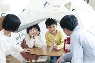 テントの中でくつろぐファミリーの写真素材 [FYI04868378]