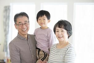 リビングで微笑むシニア夫婦と孫の写真素材 [FYI04868603]
