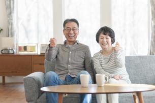 ソファーでガッツポーズをするシニア夫婦の写真素材 [FYI04868607]