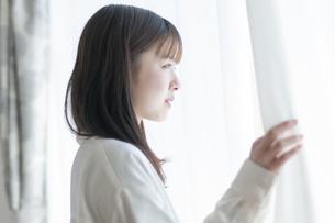 リビングの窓辺に立つ女性の写真素材 [FYI04868618]