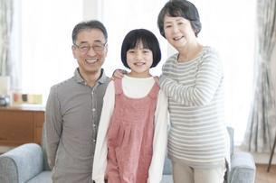 リビングで微笑む祖父母と孫の写真素材 [FYI04868619]