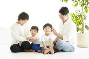 明るい室内でくつろぐ家族の写真素材 [FYI04869701]