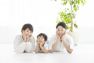 寝そべって同じポーズを取る親子3人の写真素材 [FYI04869705]