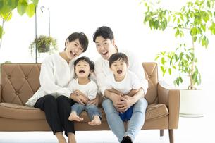ソファの上で仲良くはしゃぐ家族の写真素材 [FYI04869710]