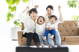 手をあげて喜ぶ親子・テレビ観戦イメージの写真素材 [FYI04869711]