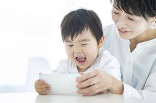 スマートフォンの画面を見る子供とお母さんの写真素材 [FYI04869779]