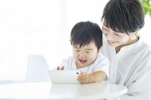 スマートフォンの画面を見る子供とお母さんの写真素材 [FYI04869785]