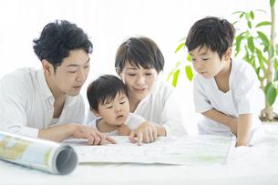 地図を使って楽しく勉強する親子・地図を使って旅行の計画を立てる親子の写真素材 [FYI04869807]