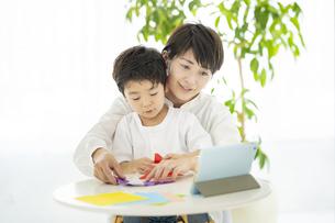 タブレットPCを見ながら折り紙をする親子の写真素材 [FYI04869810]