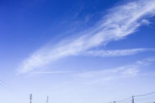 鉄塔や送電線が続く上空に大蛇に似た雲がたなびく光景の写真素材 [FYI04869860]