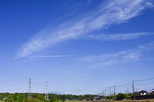 民家や鉄塔や電線が続く上空に大蛇に似た雲がたなびく光景の写真素材 [FYI04869861]