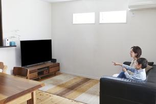 リビングでテレビを見る親子の写真素材 [FYI04870046]