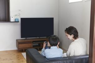 リビングでテレビを見る親子の写真素材 [FYI04870053]
