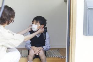玄関でマスクをする男の子と母親の手元の写真素材 [FYI04870057]