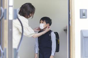玄関でマスクをする男の子と母親の手元の写真素材 [FYI04870067]