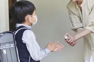 アルコール消毒をする男の子と母親の手元の写真素材 [FYI04870070]