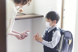 アルコール消毒をする男の子と母親の手元の写真素材 [FYI04870077]