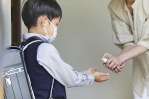 アルコール消毒をする男の子と母親の手元の写真素材 [FYI04870081]