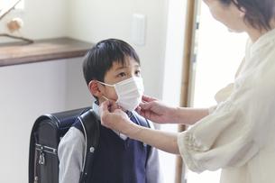 玄関でマスクをする男の子と母親の手元の写真素材 [FYI04870088]
