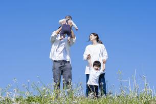 青空のもと、楽しそうにはしゃぎながら散歩する家族の写真素材 [FYI04870112]