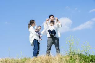青空のもと、楽しそうにはしゃぎながら散歩する家族の写真素材 [FYI04870114]