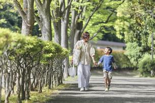 買い物バッグを持ちながら歩く親子の写真素材 [FYI04870279]