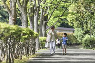 買い物バッグを持ちながら歩く親子の写真素材 [FYI04870303]