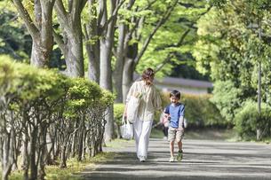 買い物バッグを持ちながら歩く親子の写真素材 [FYI04870304]