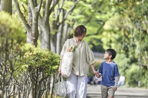 買い物バッグを持ちながら歩く親子の写真素材 [FYI04870306]