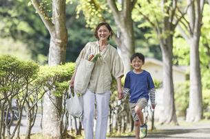 買い物バッグを持ちながら歩く親子の写真素材 [FYI04870309]