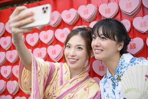 神社で縁結び祈願し写真を撮る浴衣の女性の写真素材 [FYI04870704]